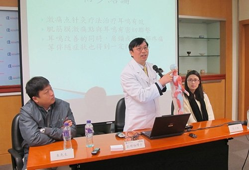 Dr. Peng Zengfu (centre) explains his clinical observations on acupuncture treatment of tinnitus with the two patients