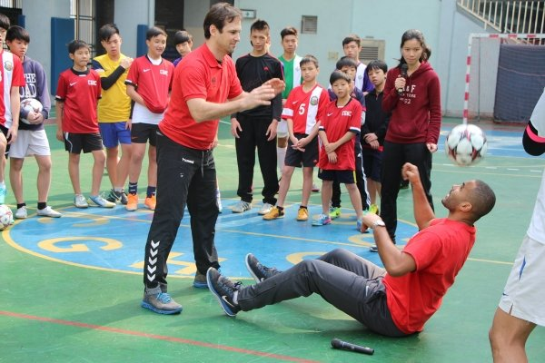 US participant Anthony Sanneh (right) who competed in the 2002 World Cup in South Korea teaches secondary students to play soccer