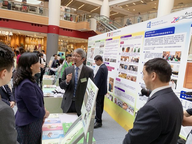 Professor Lyu Aiping (right), Dean of SCM, and Professor Bian Zhaoxiang (centre), Director of the SCM's Clinical Division and Associate Vice-President, shares his Chinese medicine knowledge at the exhibition