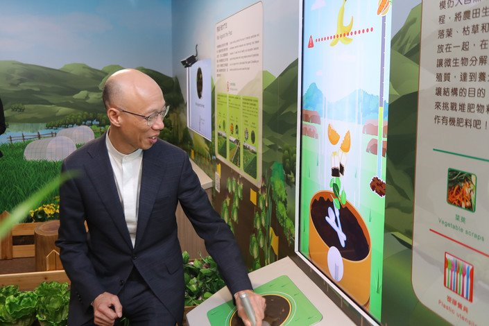 Mr Wong Kam-sing enjoys a compost game at the HKBU Sustainability Gallery.