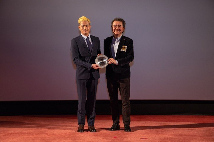 Professor Roland Chin (right) presents souvenir to Mr Aaron Kwok.