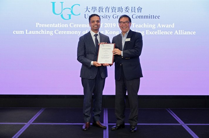 Dr Tushar Chaudhuri (left) receives the award from Mr Carlson Tong, Chairman of the UGC.
