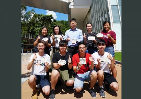 Mr Lam Long-chau (centre at back row) together with student green ambassadors install ceramic art tiles on pavements above storm drains to raise public awareness of drainage pollution